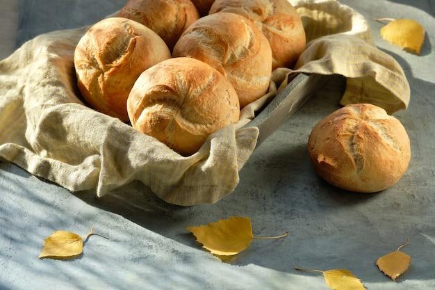Kaiser, o panini di vienna nel cestino del pane su sfondo grigio scuro con foglie di autunno gialle.