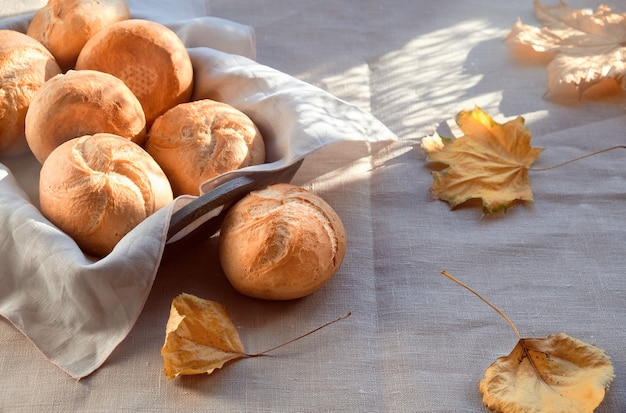 Kaiser, o vienna panini nel cestino del pane su sfondo tessile con foglie di autunno giallo.