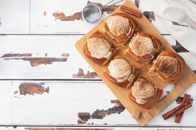 Panini alla cannella kanelbulle con crema al burro su un tavolo in legno rustico. dolci freschi fatti in casa. vista dall'alto, copia spazio.