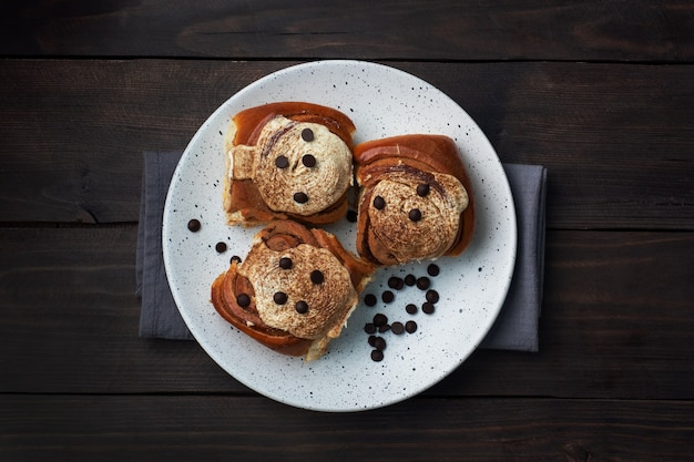 Panini alla cannella kanelbulle con crema al burro su un tavolo in legno rustico. dolci freschi fatti in casa.