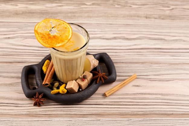 Tè karak o masala chai. popolare bevanda indiana in vetro sulla tavola di legno.