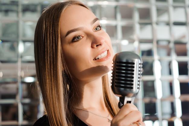 Festa karaoke. ragazza di bellezza con un canto del microfono. festa in discoteca. celebrazione.