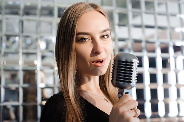 Festa karaoke. ragazza di bellezza con un microfono che canta. festa in discoteca. celebrazione.