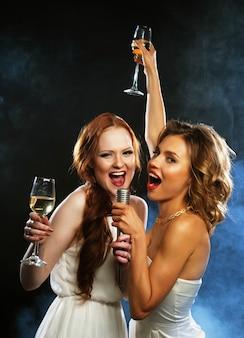 Festa di karaoke. ragazze di bellezza con un microfono che cantano e ballano sul nero.