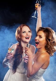 Festa di karaoke. ragazze di bellezza con un microfono che cantano e ballano su sfondo scuro.