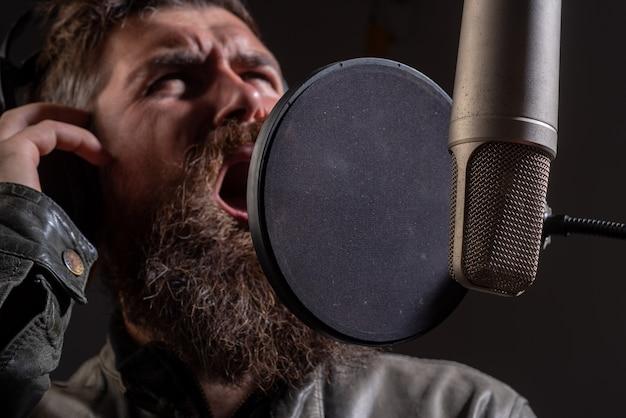 Cantante karaoke viso espressivo closeup uomo che canta con microfono musicale