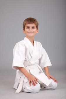 Ragazzo di karate in kimono bianco su sfondo grigio
