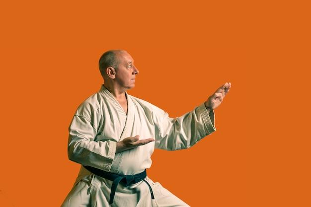 Uomo di karate in un kimono bianco con cintura nera in un allenamento individuale. foto orizzontale