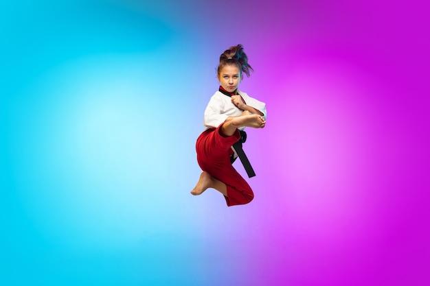 Karate, taekwondo ragazza con cintura nera isolata su sfondo sfumato in luce al neon