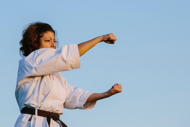 Donna di karate, lanciando un pugno, che indossa un kimono. concetto di karate e arti marziali