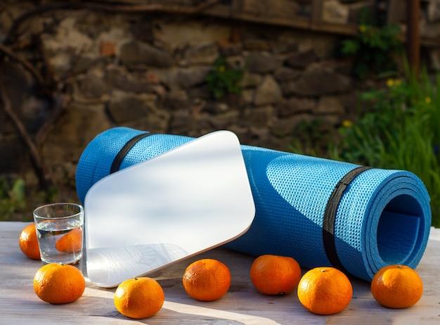 Karemat, mandarini, squame e bicchiere d'acqua su un tavolo di legno all'aperto