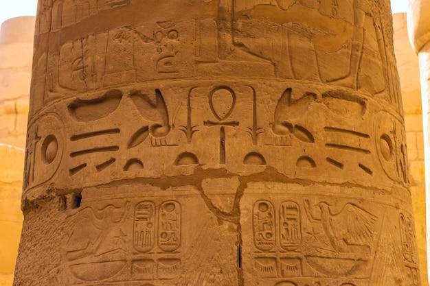 Tempio di karnak, sculture colossali dell'antico egitto nella valle del nilo a luxor, geroglifici in rilievo sulla parete.