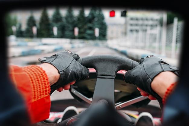 Pilota di kart sulla linea di partenza, vista con gli occhi del pilota. pista di velocità di go-kart