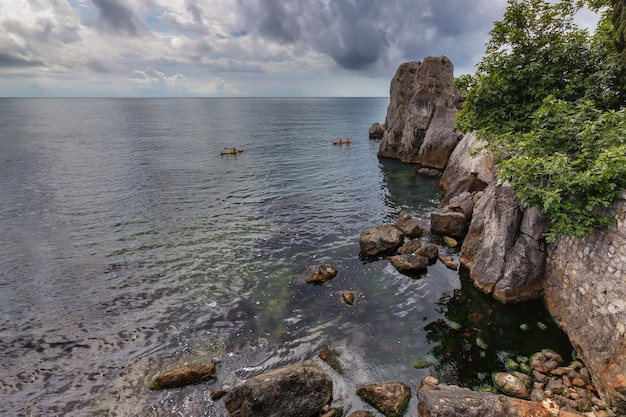 Kayak kayak vacanza sfondo baia spiaggia bella bellezza mare nero scogliera scogliera bordo Foto Premium