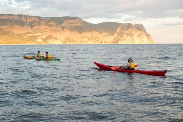 Kayak. canoa nel mare vicino all'isola con le montagne. persone in kayak nell'oceano.