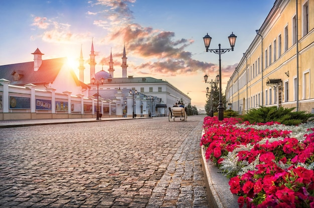 Il cremlino di kazan dall'interno si affaccia sulla moschea kul-sharif sotto i raggi del sole al tramonto, una carrozza bianca e fiori rossi