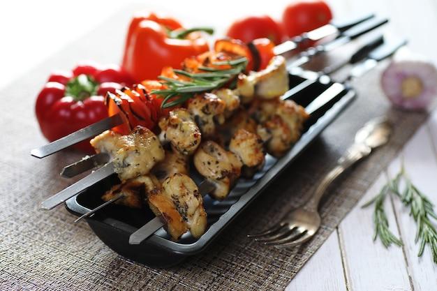 Kebab cotto su spiedini di metallo con verdure servite su tavola bianca