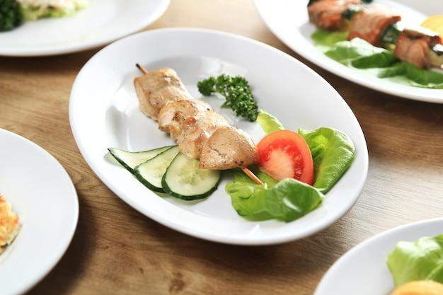 Kebab e verdure fresche su un piatto bianco