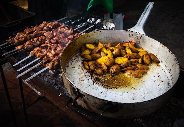 Kebab e patate arrosto in una padella capiente