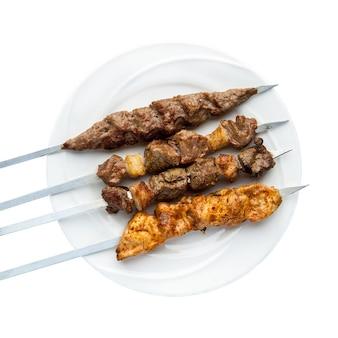 Kebab su spiedini in un piatto su sfondo bianco. vista dall'alto. isolato. barbecue