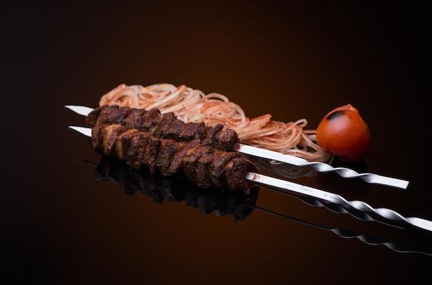 Bastoncini di kebab su spiedini con cipolla e pomodoro su sfondo scuro