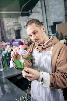 Mantieni l'attenzione. felice uomo che indossa il grembiule mentre si lavora con le piante nella boutique floreale