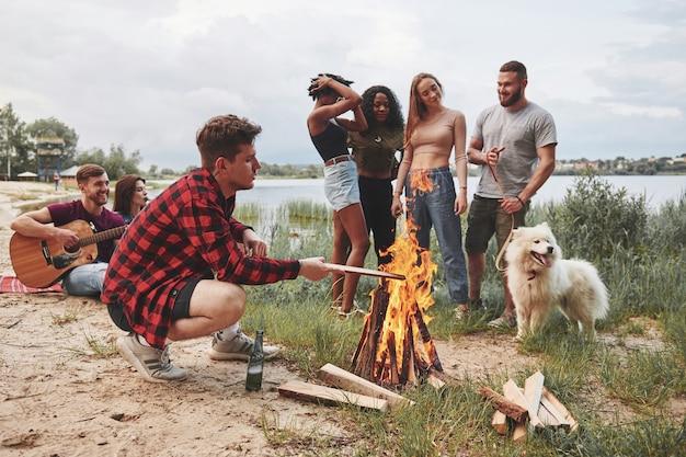 Continua a bruciare. un gruppo di persone fa un picnic sulla spiaggia. gli amici si divertono durante il fine settimana.