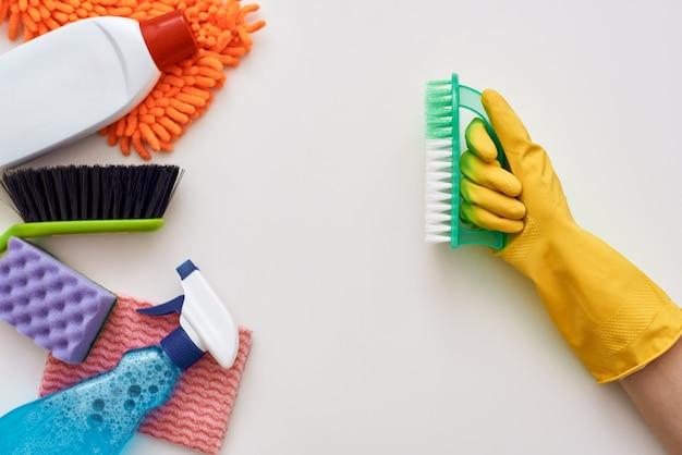 Continua a pulire. la bottiglia di pennello in mani umane ha attaccato altri oggetti isolati nella parte inferiore dell'immagine