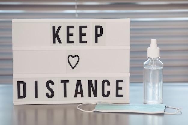 Mantieni il cartello a distanza e il disinfettante per le mani sulla scrivania vuota del posto di lavoro nell'ufficio post pandemia