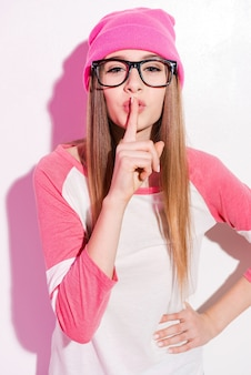 Mantieni il mio segreto! giovane donna giocosa in copricapo rosa e occhiali che tiene il dito vicino alle labbra mentre sta in piedi su sfondo bianco white