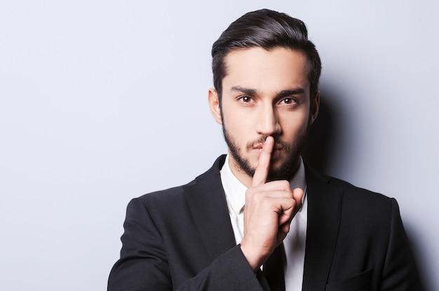 Mantieni il mio segreto! giovane serio in abiti da cerimonia che tiene il dito sulle labbra e guarda la telecamera mentre sta in piedi su uno sfondo grigio
