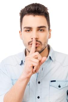 Mantieni il mio segreto! giovane serio in camicia che tiene il dito sulle labbra e guarda la telecamera mentre sta in piedi su sfondo bianco