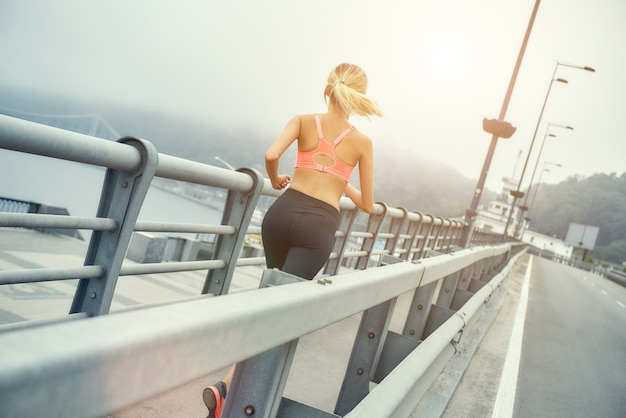 Continua a correre dietro la vista di una donna bionda carina e sicura di sé in abbigliamento sportivo che fa jogging