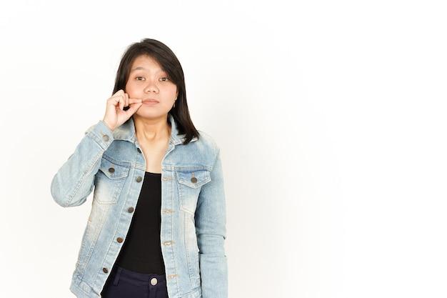 Tenere il labbro segreto chiuso della bella donna asiatica che indossa una giacca di jeans e una camicia nera isolata su bianco