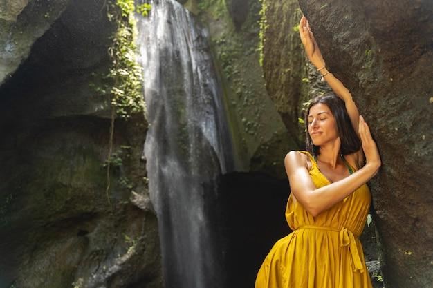 Continua a sorridere. bella ragazza bruna che si gode la sua sosta vicino alla cascata, facendo un'escursione nella natura selvaggia