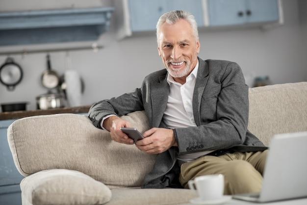 Continua a sorridere. allegro persona di sesso maschile che sente la felicità durante la digitazione del messaggio e guardando dritto verso la telecamera