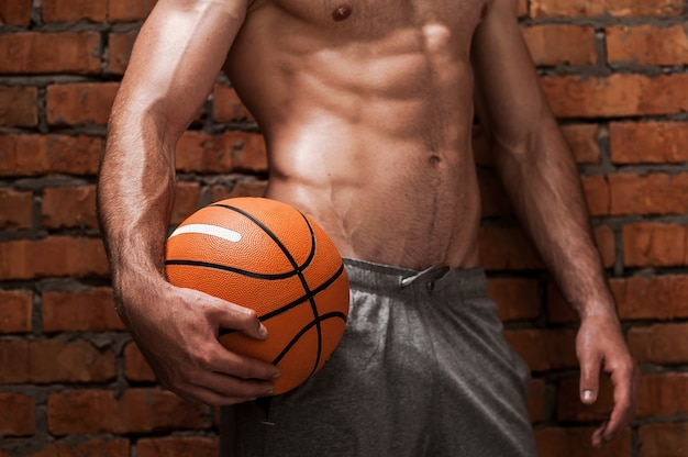 Tenere il passo in questo gioco. primo piano di giovane uomo muscoloso che tiene palla da basket