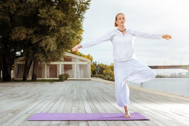 Mantenere l'equilibrio. la giovane donna in piedi su una gamba mentre fa esercizi di yoga