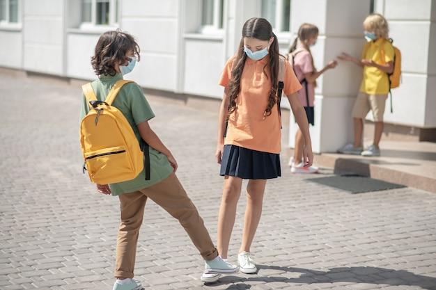 Mantenere le distanze. scolari in maschere protettive nel cortile della scuola si salutano mantenendo le distanze