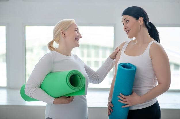 Tenersi in forma. tappeti femminili biondi e castana di yoga della tenuta femminile, discutendo di qualcosa, donna bionda che picchietta la sua amica sulla spalla