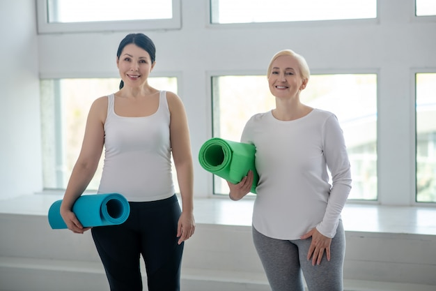 Tenersi in forma. femmina bionda e femmina castana che stanno con le coperte di yoga, sorridenti