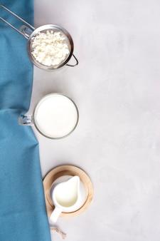 Kefir in un bicchiere, accanto a chicchi di kefir e latte su una superficie grigia in un asciugamano blu