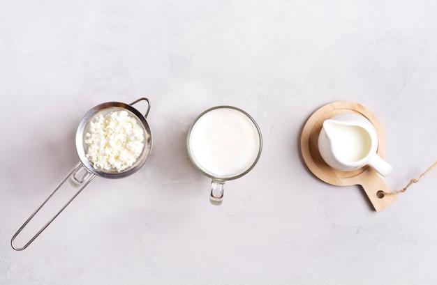 Kefir in un bicchiere, accanto a chicchi di kefir e latte su una superficie grigia