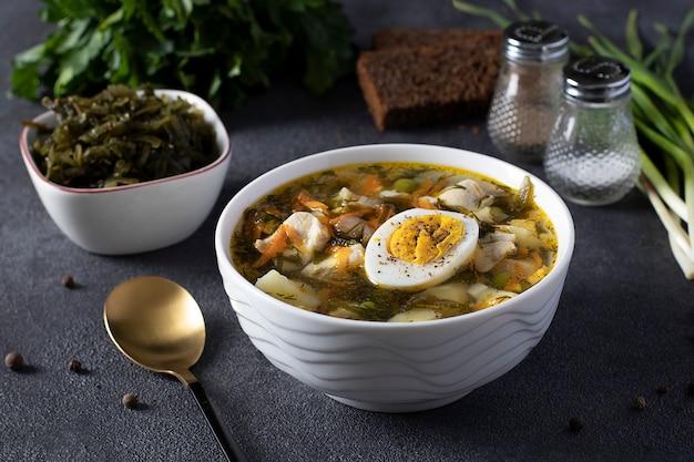 Zuppa di alghe e pollo servita con uova sode in una ciotola bianca su sfondo scuro. avvicinamento