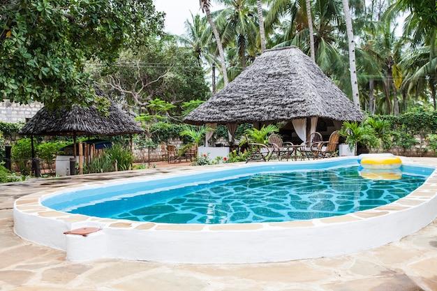 Kenia. piscina di lusso in giardino africano con sedie tipiche locali in legno sullo sfondo