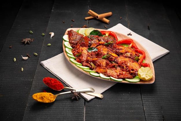 Masala di pesce del kerala realizzato con spezie fette di cocco per insaporire e sistemato in un servizio da tavola