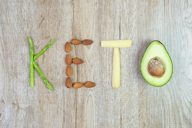 Disposizione keto di asparagi biologici, mandorle, baby mais e avocado sul fondo della tavola