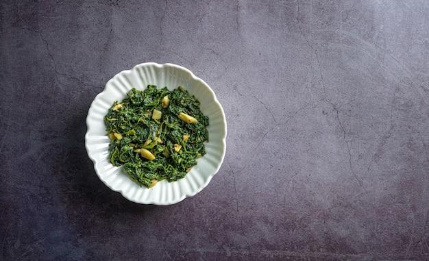 Keto diet food spinaci curry in ciotola bianca su piastrelle di ardesia nera vista dall'alto