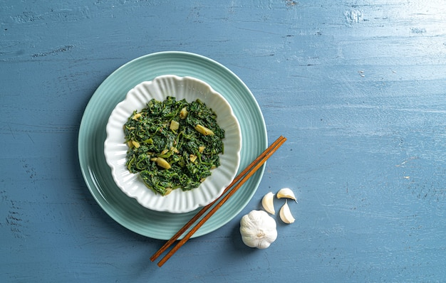 Keto dieta alimentare spinaci curry in ciotola bianca e piatto blu con bacchette e aglio su tavolo in legno blu vista dall'alto
