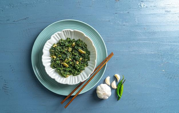 Cibo dietetico keto curry di spinaci in ciotola bianca e piatto blu con bacchette di peperoncino all'aglio su tavolo di legno blu